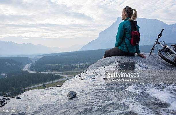 Young woman relaxes with bike on mountain ledge