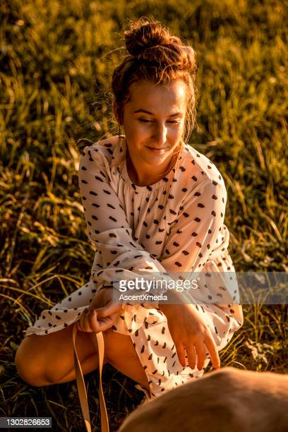 young woman relaxes with her dog in grassy meadow at sunrise - mini dress stock pictures, royalty-free photos & images