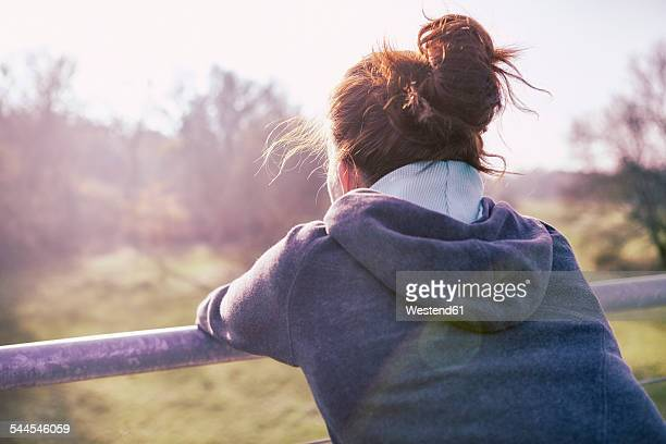 young woman relaxing after jogging, back view - acconciatura all'insù foto e immagini stock