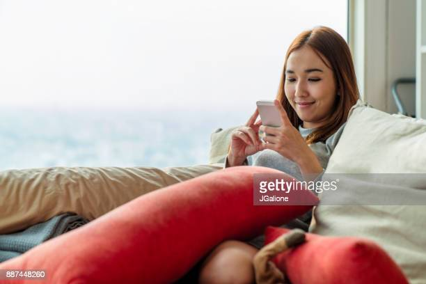 Young woman relaxing and smiling whilst looking at her phone