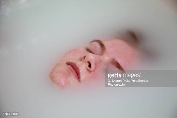 young woman relaxing and soaking in milk bath water - queimadura pele imagens e fotografias de stock