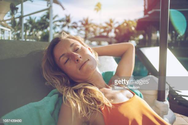 young woman relaxing and sunbathing on chaise longue at poolside in tropical climate in asia. people tranquillity zen attitude concept - women sunbathing stock photos and pictures