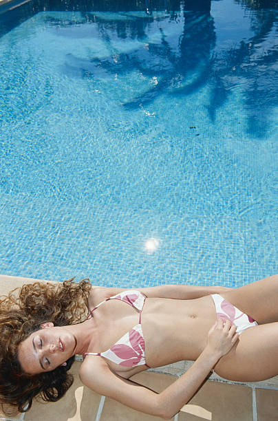 Young woman relaxing at edge of swimming pool, elevated view