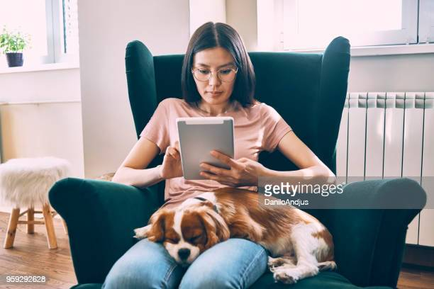 young woman relaxing at home using her tablet