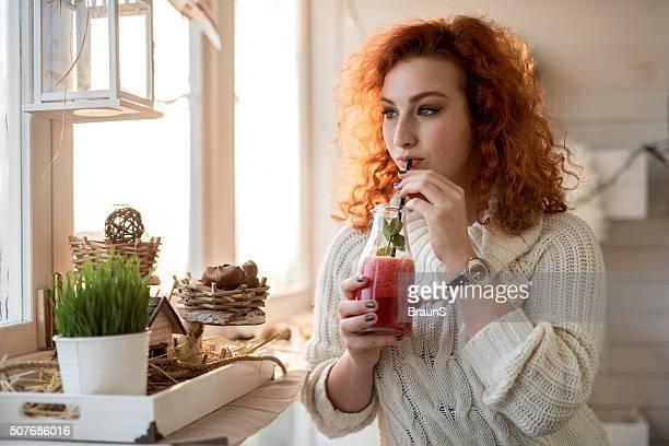 Junge Frau zu Hause zu entspannen, während Sie trinken rot-smoothie.