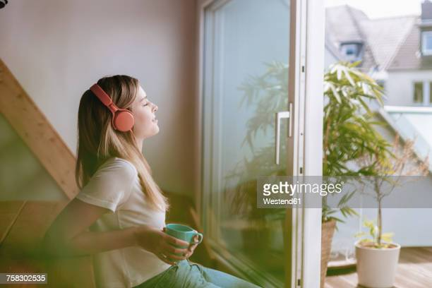 young woman relaxing at home with a cup of tea, listening music - zuhören stock-fotos und bilder
