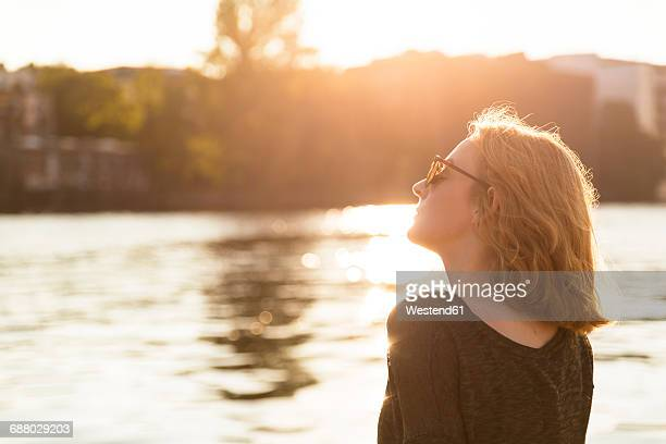 young woman relaxing at riverside in the evening twilight - riverbank - fotografias e filmes do acervo