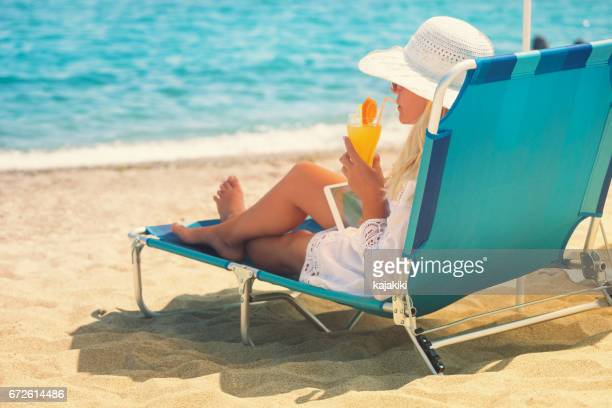 young woman relaxing at the beach - chaise longue stock photos and pictures