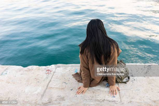 Young woman relaxing at the shoreline of Palmeral de las sorpresas port in Malaga, Andalusia, Spain, Blue water and sunset in the background.