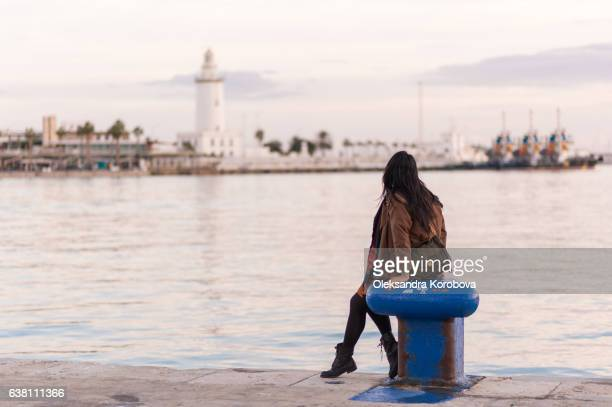 young woman relaxing at the shoreline of palmeral de las sorpresas port in malaga, andalusia, spain, blue water and sunset in the background. - malaga fotografías e imágenes de stock