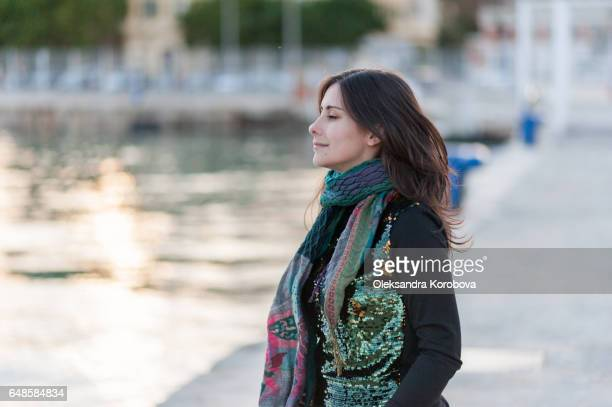 young woman relaxing at the shoreline of palmeral de las sorpresas port in malaga, andalusia, spain. - istock stock pictures, royalty-free photos & images