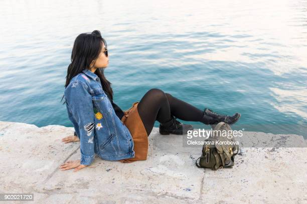 Young woman relaxing at the shoreline of Palmeral de las sorpresas port in Malaga, Andalusia, Spain.