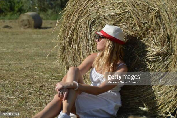 Young Woman Relaxing By Hay Bales On Field