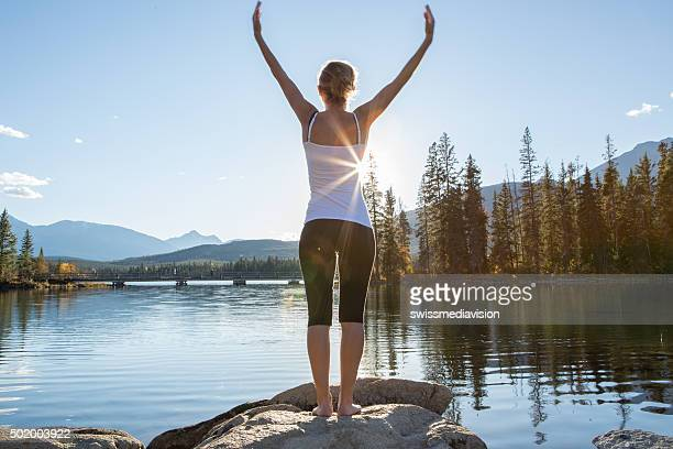Young woman relaxing by the lake, arms outstreched
