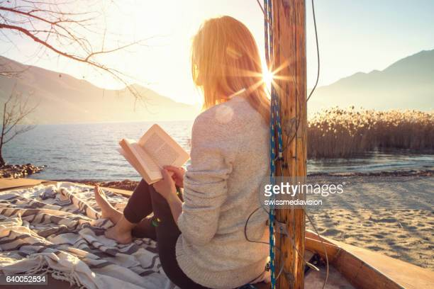 young woman relaxing by the lake reading book - lesen stock-fotos und bilder