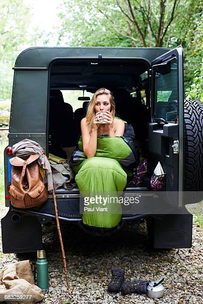 young woman relaxing drinking tea in 4 wheel drive