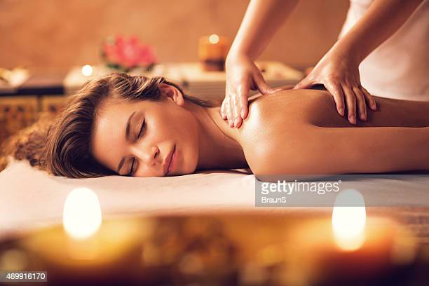 young woman relaxing during back massage at the spa. - massage therapist stock pictures, royalty-free photos & images