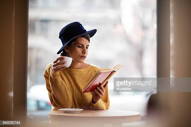 Jeune femme se détendant dans un café avec café et réserver.