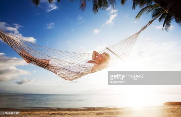 Jovem mulher relaxante na cama de rede na praia tropical.