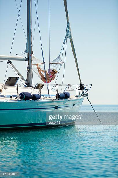 young woman relaxing in a hammock on sailboat