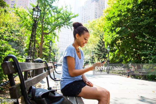 Young woman relaxing in a park in New York using mobile phone