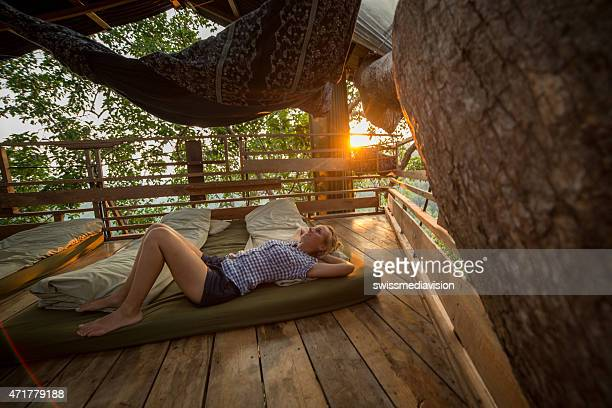young woman relaxing in a tree house at sunset - tree house stock pictures, royalty-free photos & images