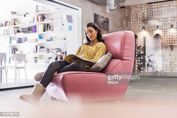 Young woman relaxing in armchair and reading.