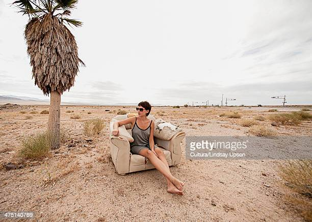 Young woman relaxing in armchair in desert