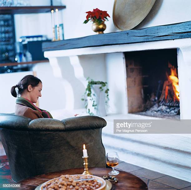 Young woman relaxing in armchair in front of fireplace