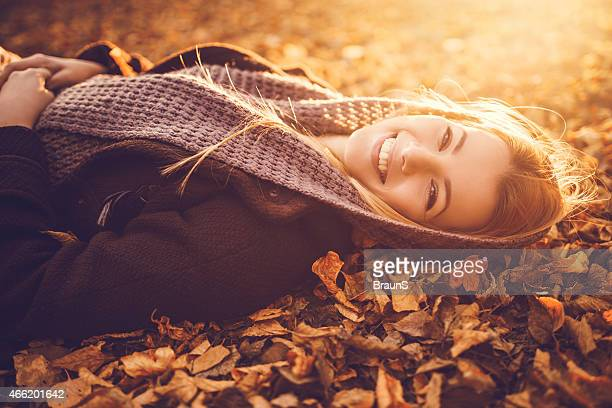 Young woman relaxing in autumn leaves at the park.