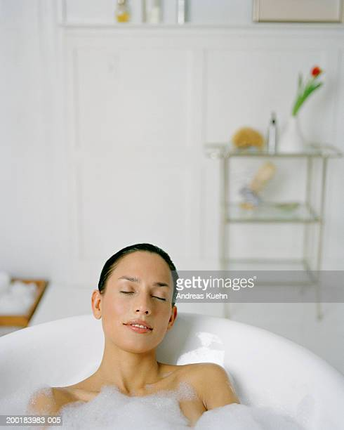 Young woman relaxing in bath with eyes closed