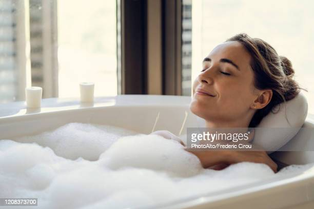 young woman relaxing in bathtub - bubble bath stock pictures, royalty-free photos & images