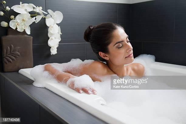 young woman relaxing in bathtub - 後ろで束ねた髪 ストックフォトと画像