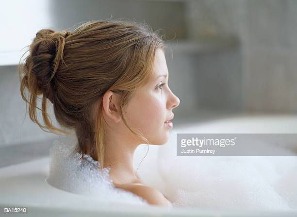 Young woman relaxing in bubble bath, profile, close-up