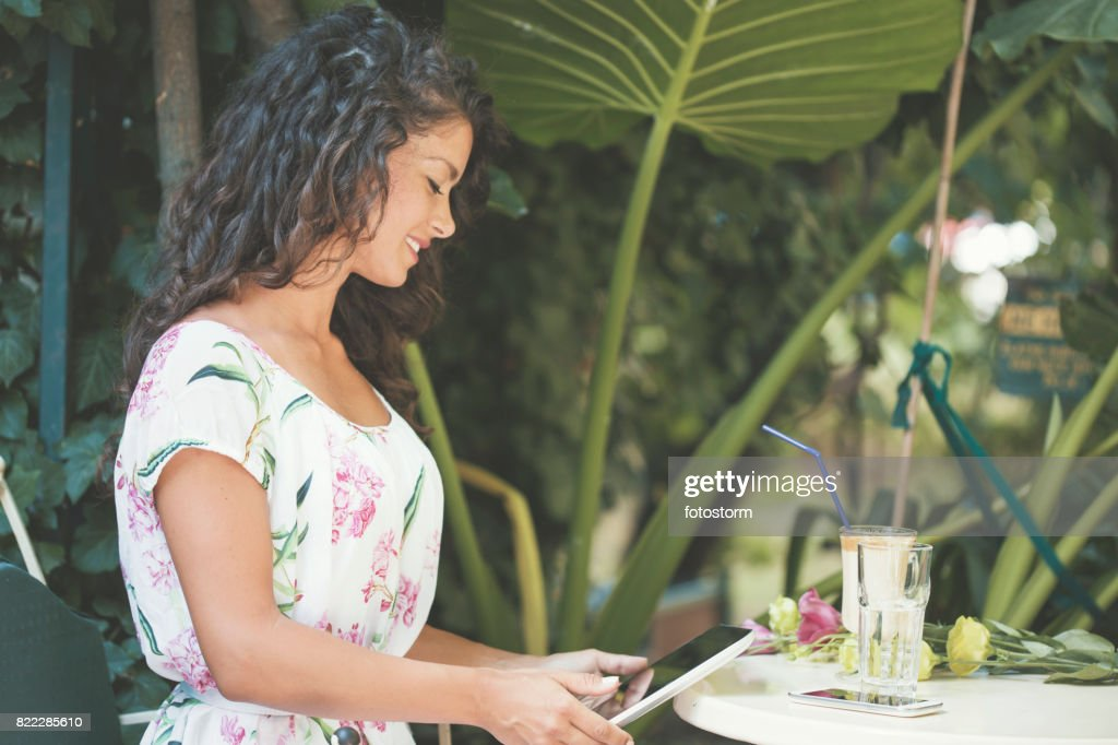 Young woman relaxing in cafe garden : Stock Photo