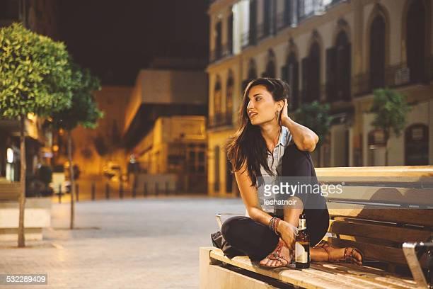Junge Frau entspannt in den Abend auf der Bank