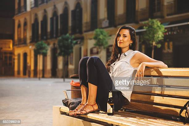 young woman relaxing in evening on the bench - sandal stock pictures, royalty-free photos & images