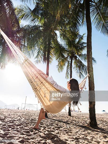 Young woman relaxing in hammock at the beach.