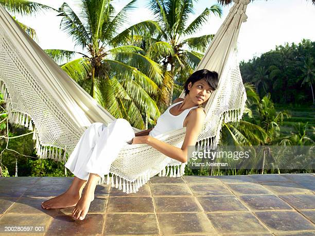 Young woman relaxing in hammock on terrace