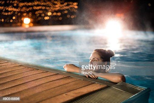 jovem mulher relaxante na piscina de inverno quente durante a noite foto de stock getty images. Black Bedroom Furniture Sets. Home Design Ideas