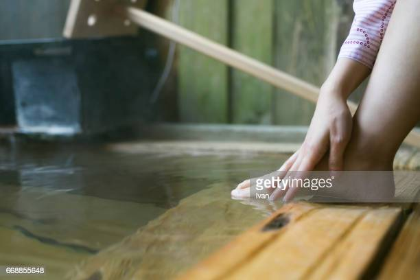 A Young Woman Relaxing in Japanese Style Hot Spring with Bare Feet