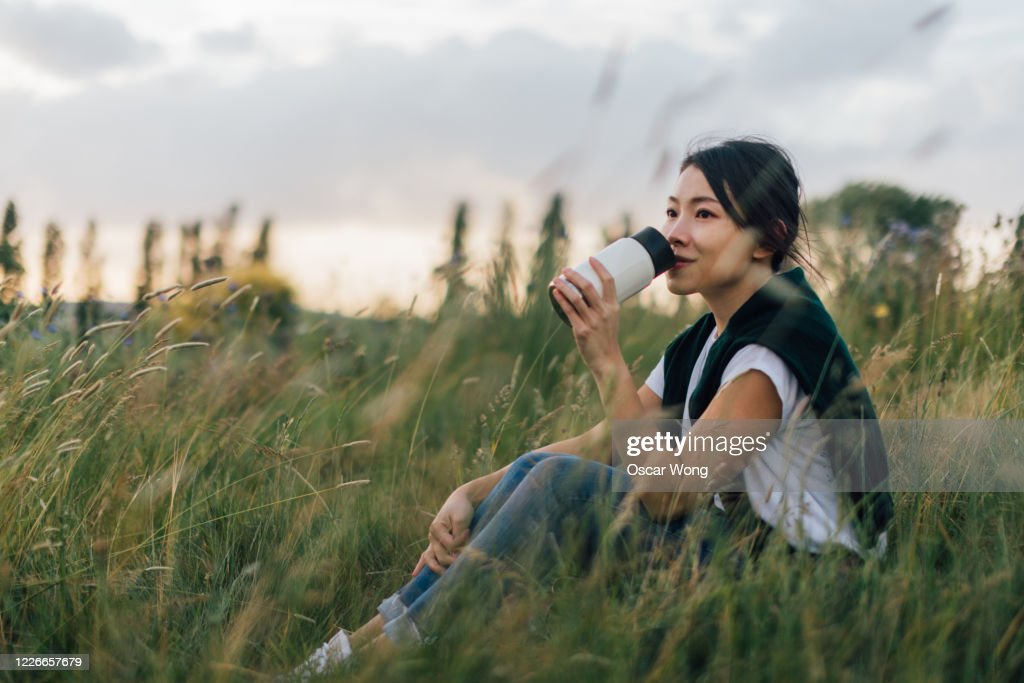 Young Woman Relaxing In Nature, Drinking With A Reusable Coffee Cup : Stock Photo