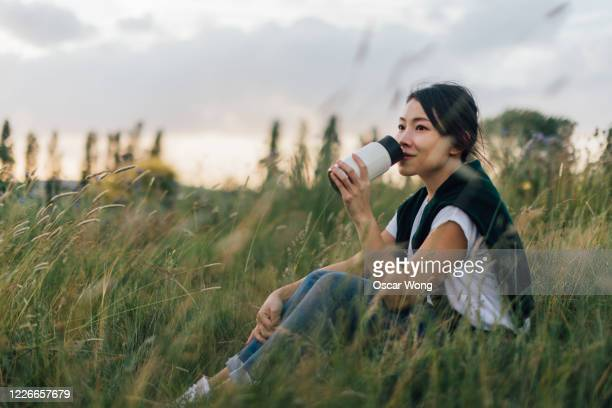 young woman relaxing in nature, drinking with a reusable coffee cup - sustainability stock pictures, royalty-free photos & images