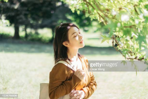 young woman relaxing in nature with eye closed - japanese ethnicity stock pictures, royalty-free photos & images
