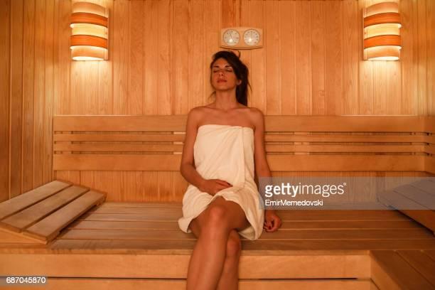 junge frau in sauna im wellnessbereich entspannen - sauna stock-fotos und bilder