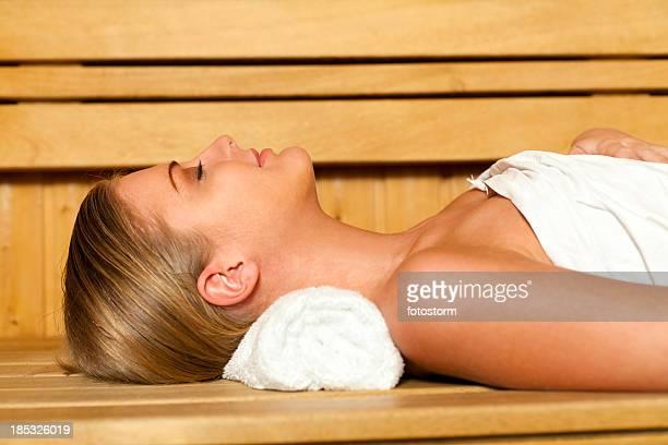 Jovem mulher relaxante na sauna