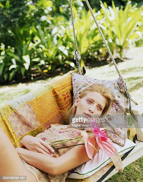 Young woman relaxing in swing chair, holding flower, outdoors