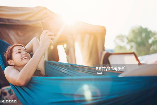 Young woman relaxing in the hammock and texting