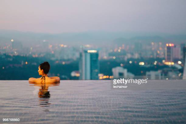young woman relaxing in the pool as the sun sets above kuala lumpur - petronas towers stock pictures, royalty-free photos & images