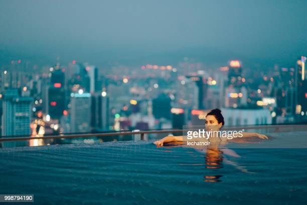 Young woman relaxing in the pool as the sun sets above Kuala Lumpur